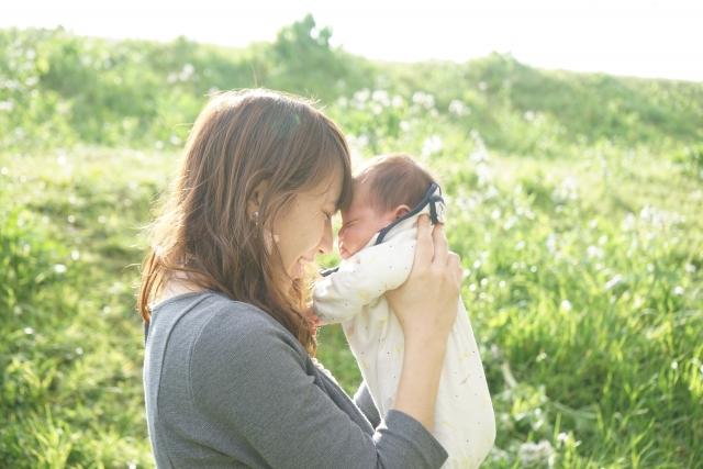 野原で新生児を抱っこする母親